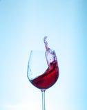 在玻璃的红葡萄酒在蓝色背景 bever的概念 库存照片