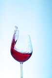 在玻璃的红葡萄酒酒在蓝色背景 概念  库存图片