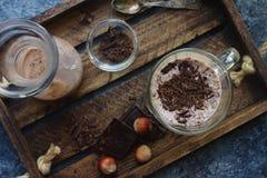 在玻璃的自创巧克力牛奶震动在木背景 免版税库存图片