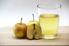 在玻璃的苹果汁在木头 免版税库存图片