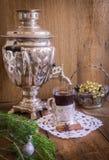 在玻璃的茶与沿海航船和在木背景的俄国俄国式茶炊 家庭圣诞节装饰 图库摄影