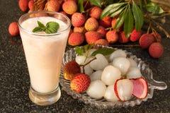 在玻璃的荔枝汁液 在一块玻璃板的新鲜的水多的lychee果子 图库摄影