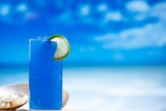 在玻璃的蓝色融雪冰在海海滩背景 免版税库存图片