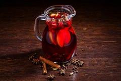 在玻璃的被仔细考虑的酒在木桌上 库存图片