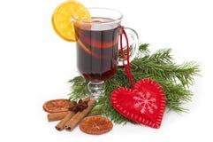 在玻璃的被仔细考虑的酒用肉桂条、在白色和心脏隔绝的圣诞树 免版税库存图片
