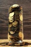 在玻璃的超载硬币 免版税库存图片