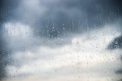 在玻璃的雨下落与黑暗的云彩 图库摄影