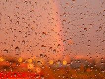 在玻璃的雨下落 背景彩虹和日落 库存照片
