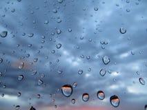 在玻璃的雨下落 免版税库存图片