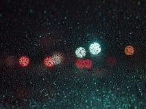 在玻璃的雨珠在色的斑点迷离背景  库存照片