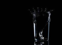 在玻璃的水与水飞溅能量 图库摄影