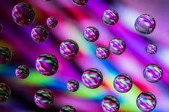 在玻璃的水滴有五颜六色的背景 免版税图库摄影