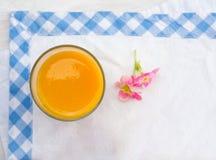 在玻璃的黄色汁液与桃红色花 免版税库存图片