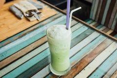 在玻璃的绿色鸡尾酒与秸杆在多彩多姿的木桌上站立 免版税库存图片