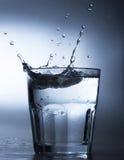 在水玻璃的水飞溅 免版税库存照片