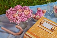在玻璃盘子的桃红色花在天蓝色布料 免版税库存图片