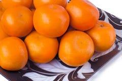 在玻璃盘的大成熟蜜桔在白色背景。 库存图片
