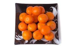 在玻璃盘的大成熟蜜桔在白色背景。 库存照片