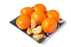 在玻璃盘的大成熟蜜桔在白色背景。 免版税库存照片