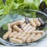 在玻璃盘的膳食补充剂胶囊与新vegetabl 库存照片