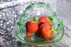 在玻璃盘的草莓有闪耀的背景 库存图片