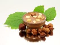 在玻璃碗的巧克力用榛子和叶子 免版税库存照片