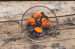 在玻璃碗的干果子在木背景 库存图片