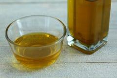 在玻璃碗的橄榄油在木背景 库存照片