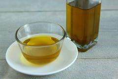 在玻璃碗的橄榄油在木背景 图库摄影