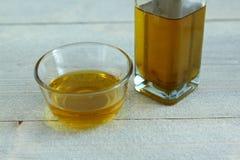 在玻璃碗的橄榄油在木背景 免版税图库摄影