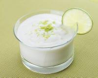 在玻璃碗的石灰奶油甜点在绿色背景 免版税图库摄影