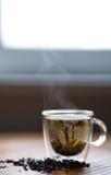 在玻璃窗前面的热的蒸汽的绿茶 免版税图库摄影