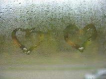 在玻璃窗和雨下落的被绘的心脏 免版税库存照片