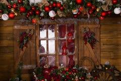 在玻璃窗的圣诞节装饰与木制框架 免版税库存照片