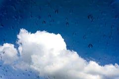水滴在玻璃窗的在蓝天 免版税图库摄影
