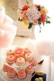 在玻璃立场的桃红色杯形蛋糕 免版税库存照片