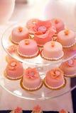 在玻璃立场的桃红色杯形蛋糕 库存照片