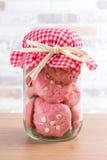 在玻璃罐,有格子花呢披肩织品的盖帽的草莓曲奇饼 免版税库存照片