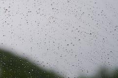 在玻璃背景的雨珠 免版税库存图片