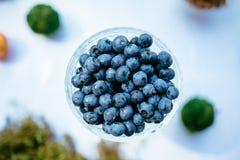 在玻璃花瓶的一些个蓝莓在白色背景 免版税库存照片