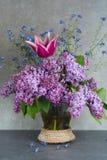 在玻璃花瓶的五颜六色的花束有紫色丁香,桃红色郁金香的和 库存照片
