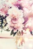 在玻璃花瓶的可爱的牡丹束在与bokeh照明设备的桌上 浪漫花花束,正面图 图库摄影