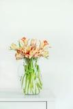 在玻璃花瓶的可爱的郁金香束在白色墙壁的白色桌上 家庭内部概念 免版税库存照片