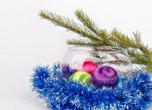 在玻璃花瓶的圣诞节球在白色背景的闪亮金属片中 库存图片
