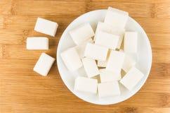 在玻璃茶碟的块糖在木桌上 免版税库存照片