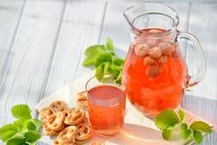 在玻璃蒸馏瓶的自创草莓蜜饯用在白色木桌上的椒盐脆饼在庭院里 免版税库存照片
