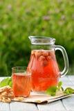 在玻璃蒸馏瓶的自创草莓蜜饯用在白色木桌上的椒盐脆饼在庭院里 免版税图库摄影