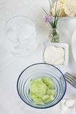 在玻璃蓝色碗的黄瓜沙拉在白色布料 库存照片