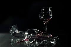 在玻璃表上溢出的残破的玻璃杯的红葡萄酒隔绝在黑色 库存图片