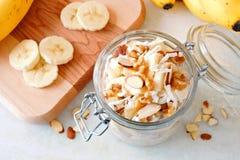 在玻璃装于罐中的瓶子,向下看法的香蕉坚果隔夜燕麦 图库摄影